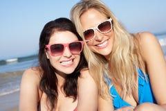 Två kvinnor som tycker om strandferie Arkivfoton