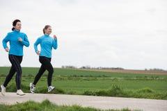 Två kvinnor som utomhus joggar Arkivfoto
