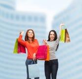 Två le tonårs- flickor med shoppingpåsar Royaltyfri Bild