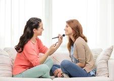 Två le tonårs- flickor som hemma applicerar smink Fotografering för Bildbyråer