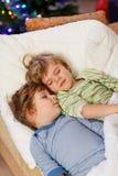 Två lilla blont kopplar samman pojkar som sover i säng på jul Arkivfoto
