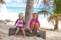 Två lilla systrar i trevliga baddräkter har gyckel på Fotografering för Bildbyråer