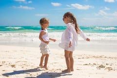 Två lilla systrar i vit kläder har gyckel på Arkivfoton