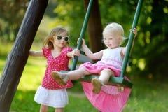 Två lilla systrar som har gyckel på en gunga Arkivfoton