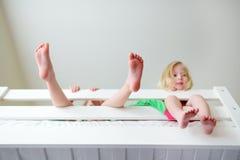Två lilla systrar som omkring bedrar, spelar och har gyckel i tvilling- britssäng Royaltyfri Foto