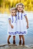 Tv? lilla systrar som skrattar och kramar p? varm och solig sommardag tv? systrar i vita kl?nningar n?ra vattnet fotografering för bildbyråer