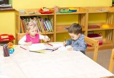 Två lilla ungar som drar med färgrika blyertspennor i förträning på tabellen flicka- och pojketeckning i dagis Arkivbild