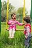Två lilla ungar som har gyckel på en gunga Royaltyfri Foto