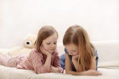 Tv? liten flickasystrar 7 och 8 gamla ?r h?ller ?gonen p? en eBook och en smartphone hemma p? soffan med deras katt fotografering för bildbyråer