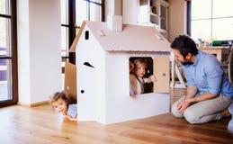 Tv? litet barnbarn med fadern som spelar med pappershuset inomhus hemma royaltyfri fotografi