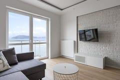 Tv living room with balcony. Gray sofa and decorative brick wall stock photo