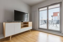 Tv living room with balcony. Grey tv living room with simple cabinet, floor panels and balcony royalty free stock image