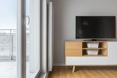 Tv living room with balcony. Grey wall, wooden cabinet and floor panels royalty free stock photography