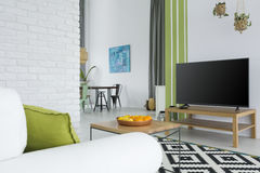 Tv living room with sofa. Tv living room with white sofa, table and brick wall Royalty Free Stock Photo