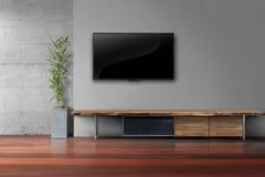 TV llevada en la pared gris con la tabla de madera en sitio del livg Fotos de archivo