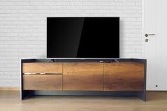 TV llevada en soporte de la TV en sitio vacío con la pared de ladrillo blanca adorne Foto de archivo libre de regalías
