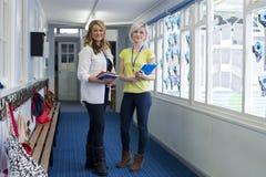 Två lärare i skolakorridor Royaltyfri Foto