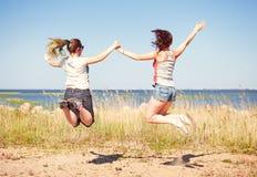 Två lyckliga flickor som hoppar på stranden Arkivbild