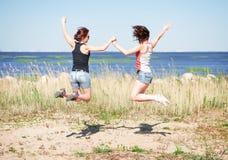 Två lyckliga flickor som hoppar på stranden Royaltyfria Bilder