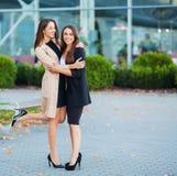 Tv? lyckliga flickor som tillsammans reser utland och att b?ra resv?skabagage i flygplats arkivbild