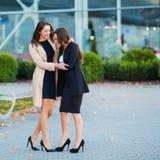Tv? lyckliga flickor som tillsammans reser utland och att b?ra resv?skabagage i flygplats arkivbilder
