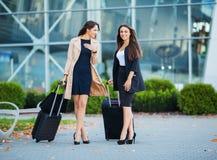Tv? lyckliga flickor som tillsammans reser utland och att b?ra resv?skabagage i flygplats fotografering för bildbyråer
