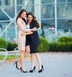 Tv? lyckliga flickor som tillsammans reser utland och att b?ra resv?skabagage i flygplats royaltyfri foto