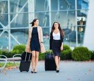 Tv? lyckliga flickor som tillsammans reser utland och att b?ra resv?skabagage i flygplats royaltyfri fotografi
