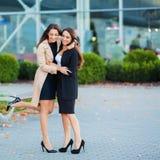 Tv? lyckliga flickor som tillsammans reser utland och att b?ra resv?skabagage i flygplats arkivfoto