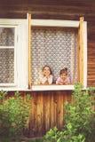 Två lyckliga gulliga flickor som har gyckel i fönster hemma i solig dag Arkivfoton