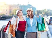 Två lyckliga härliga flickor med omfamning för shoppingpåsar i staden Arkivbilder