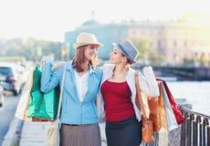 Två lyckliga härliga flickor med omfamning för shoppingpåsar i staden Arkivfoton