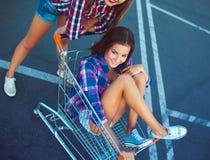 Två lyckliga härliga tonåriga flickor som utomhus kör shoppingvagnen Fotografering för Bildbyråer