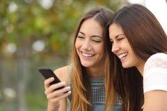 Två lyckliga kvinnavänner som delar en smart telefon Arkivbilder