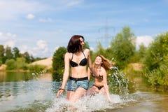 Två lyckliga kvinnor som har gyckel på sjön i sommar Arkivfoton