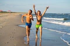 Två lyckliga pojkar som kör på havet, sätter på land på sommar med lyftt ar Royaltyfri Bild