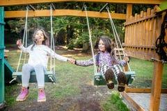 Två lyckliga små flickor som svänger på gungan Royaltyfri Bild