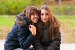 Två lyckliga tonårs- flickor som har gyckel i parken Arkivbild