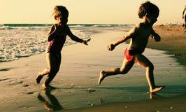 Två lyckliga ungar som spelar på stranden Arkivbild