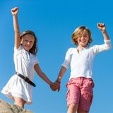 Två lyckliga ungar som utomhus lyfter händer. Arkivfoton