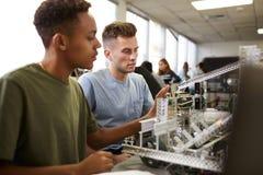 Tv? manliga universitetsstudenter som bygger maskinen i vetenskapsrobotteknik eller iscens?tter grupp arkivfoto