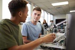 Tv? manliga universitetsstudenter som bygger maskinen i vetenskapsrobotteknik eller iscens?tter grupp fotografering för bildbyråer