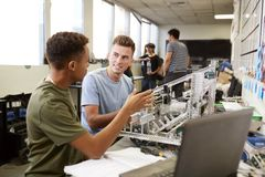 Tv? manliga universitetsstudenter som bygger maskinen i vetenskapsrobotteknik eller iscens?tter grupp royaltyfri bild