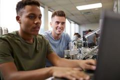 Tv? manliga universitetsstudenter som bygger maskinen i vetenskapsrobotteknik eller iscens?tter grupp arkivfoton