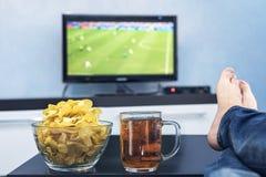 TV, match de football de observation de télévision à la TV avec des casse-croûte et alcool détendez devant la TV Une fan d'observ image stock