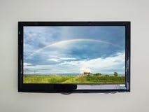 TV menée sur le fond de mur avec l'arc-en-ciel dans le ciel Photo libre de droits