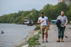 Två män går och dricker kaffe Arkivfoton