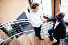 Två män i modern kontorsbyggnad som skakar händer och att le Arkivfoto