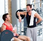 Två män på en sportidrottshall kopplade av efter kondition Arkivfoto