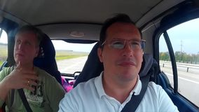 Två män som gör provdrev av den använda bilen arkivfilmer